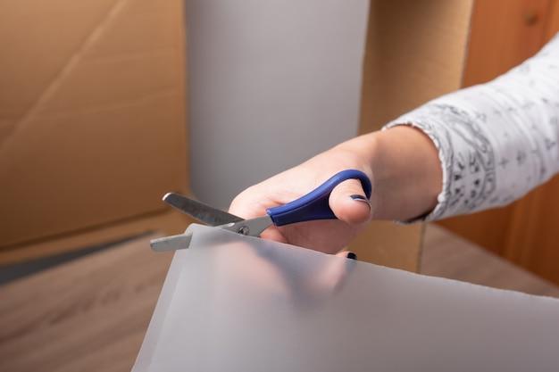 Mão de mulher cortando com uma tesoura lenço de papel e espaço de cópia