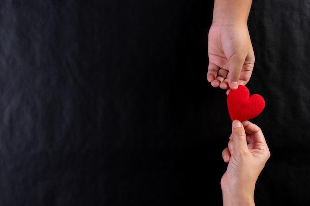 Mão de mulher dando coração vermelho para criança. dia internacional do conceito de caridade. copie o espaço.