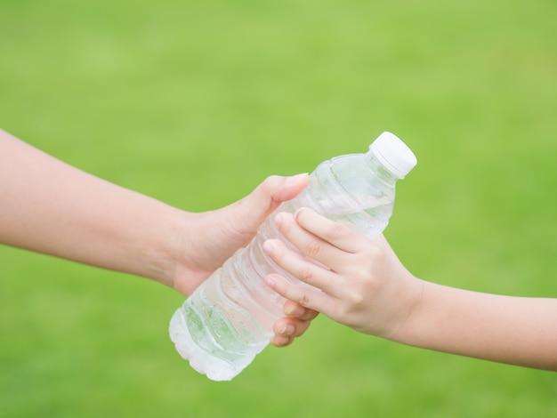 Mão de mulher dando garrafa de água fresca para criança no fundo de grama verde