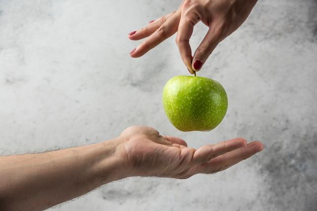 Mão de mulher dando maçã para mão de homem.