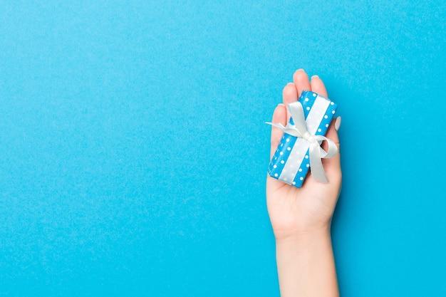 Mão de mulher dar caixa de presente de dia dos namorados, vista superior