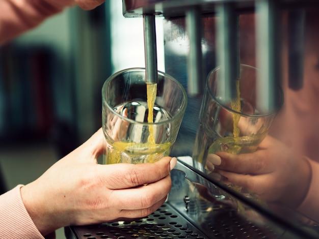 Mão de mulher de colheita derramando bebida em vidro