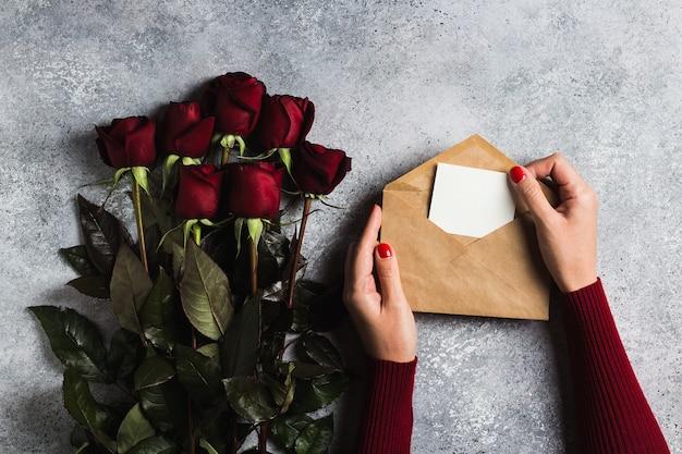 Mão de mulher de dia dos namorados segurando a carta de amor de envelope com dia das mães de cartão