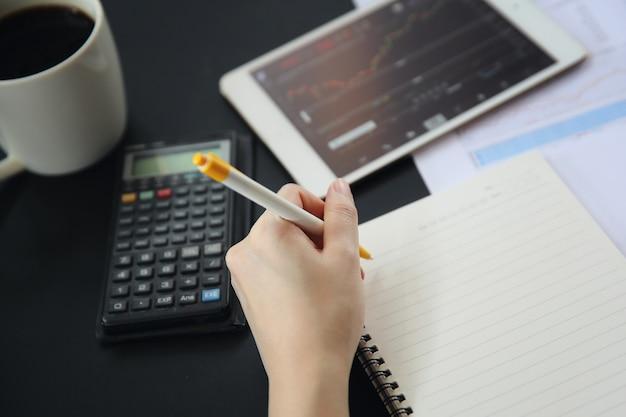 Mão de mulher de escritório trabalhando no tablet de negócios papéis e café