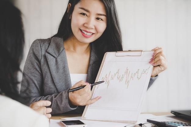 Mão de mulher de negócios asiáticos feliz apontando no gráfico financeiro em uma sala de reunião