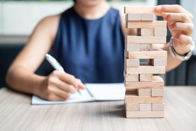 Mão de mulher de negócios, colocando ou puxando o bloco de madeira