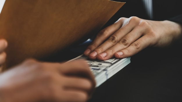 Mão de mulher de negócios com dinheiro de suborno para funcionários do governo.
