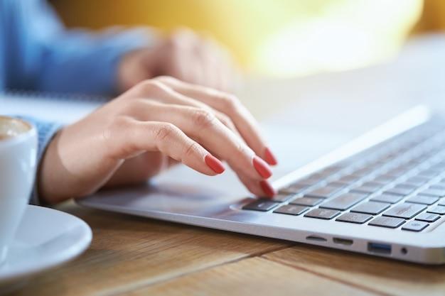 Mão de mulher de negócios digitando no teclado do laptop