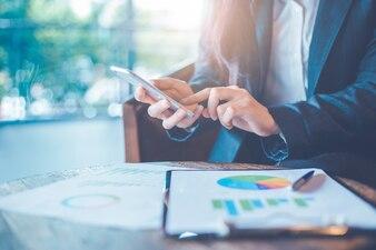 Mão de mulher de negócios estão usando smartphone
