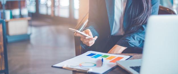 Mão de mulher de negócios estão usando telefones celulares e trabalham em tabelas e gráficos que mostram resultados no escritório.