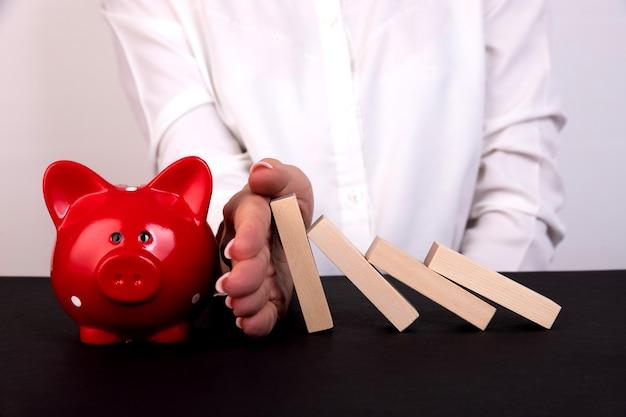 Mão de mulher de negócios impedindo a queda de blocos de madeira ou dominó gestão de risco empresarial