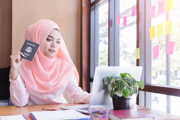 Mão de mulher de negócios muçulmano linda nos segurando passaporte planejando viajar.