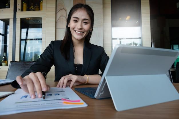 Mão de mulher de negócios segurando a caneta e apontando a papelada financeira com documento financeiro.