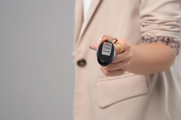 Mão de mulher de negócios, segurando a chave inteligente em fundo cinza