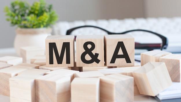 Mão de mulher de negócios segurando m e uma palavra com bloco de cubo de madeira. fusões e aquisições, informações, conceitos de comunicação