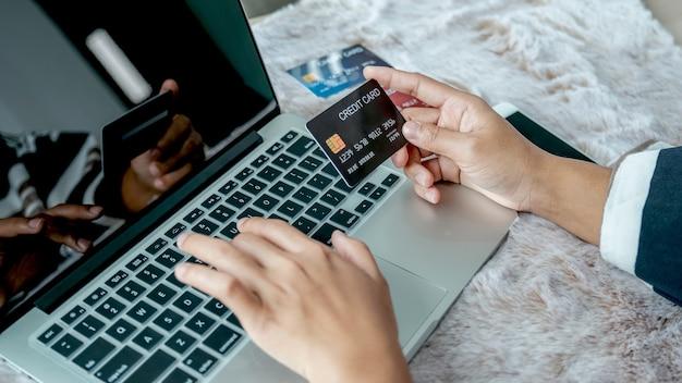 Mão de mulher de negócios segurando o cartão de crédito para fazer compras online em casa.