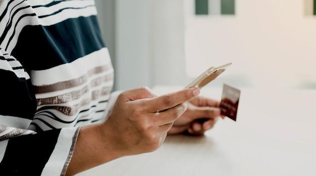 Mão de mulher de negócios segurando o smartphone e o cartão de crédito para fazer compras online em casa.