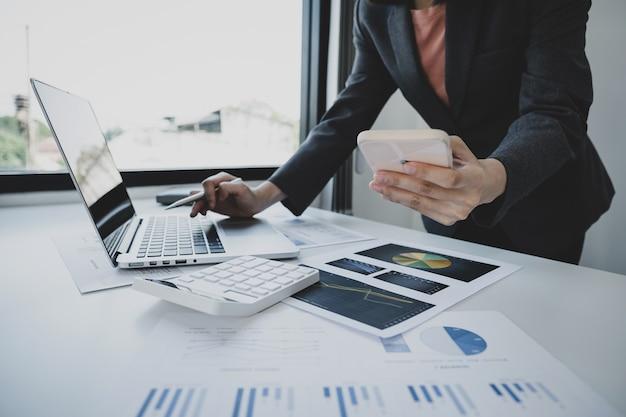 Mão de mulher de negócios segurando smartphone, análise do gráfico com calculadora e laptop no escritório em casa para definir metas de negócios desafiadoras