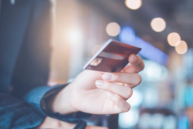 Mão de mulher de negócios segurando um cartão de crédito.