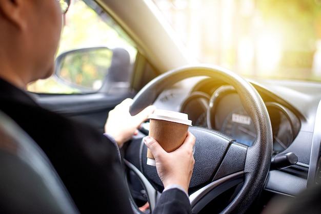 Mão de mulher de negócios segurando uma xícara de café para levar, ela está dirigindo de manhã