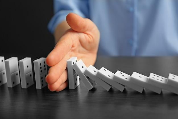 Mão de mulher de negócios tentando parar de derrubar o dominó na mesa