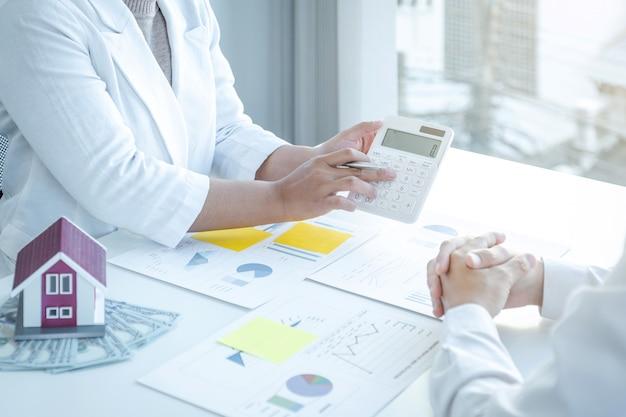 Mão de mulher de negócios usa calculadora e reunião de equipe para planejar estratégias para aumentar a receita do negócio.