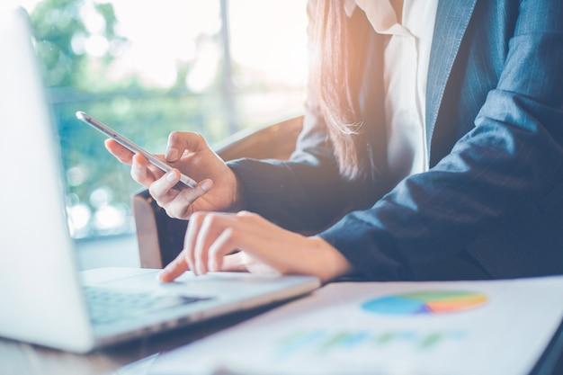 Mão de mulher de negócios usa um telefone para trabalhar em tabelas e gráficos que mostram resultados.