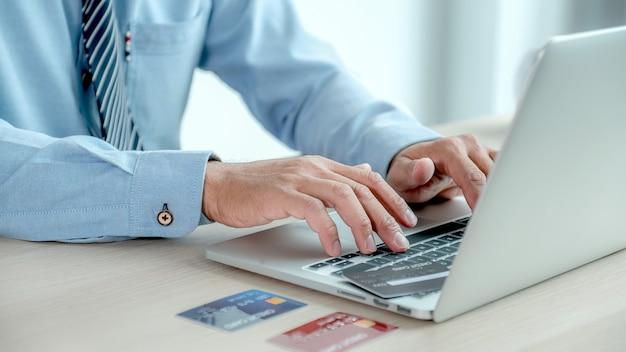 Mão de mulher de negócios usar um laptop e segurando um cartão de crédito para fazer compras online em casa.