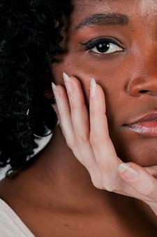 Mão de mulher de pele clara tocando o queixo do amigo feminino africano
