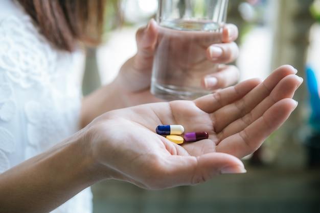 Mão de mulher derrama as pílulas de medicamento fora da garrafa