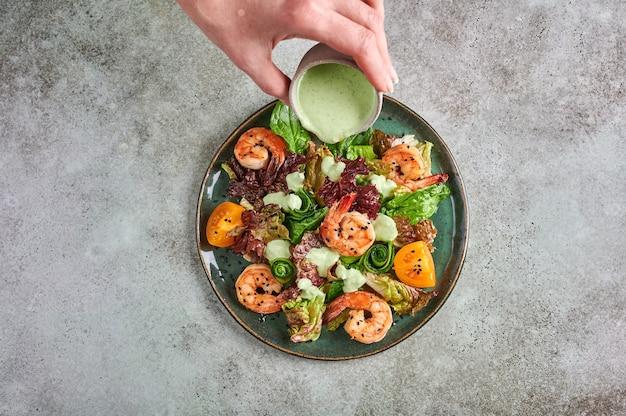 Mão de mulher derrama molho na salada com camarão frito, tomate amarelo, rúcula, espinafre, alface e molho em um prato de cerâmica
