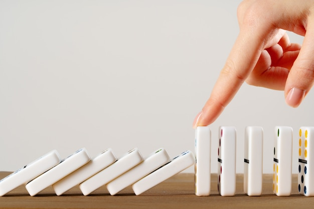 Mão de mulher derrubando dominós. conceito de negócio de reação em cadeia
