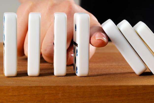 Mão de mulher derrubando dominós