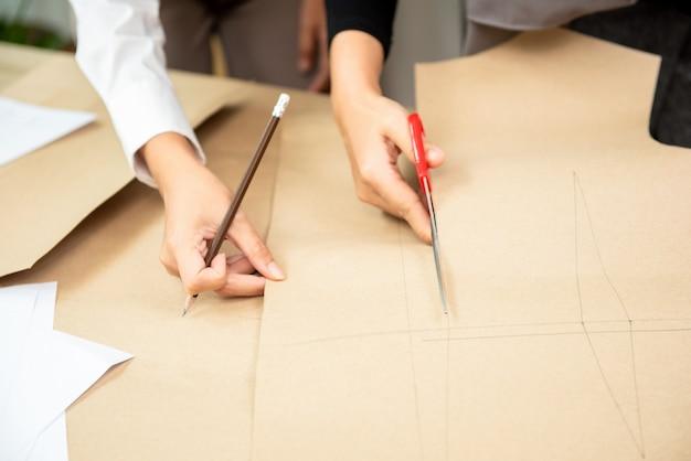 Mão, de, mulher, desenhador moda, corte, roupas, papel, padrão, com, tesouras