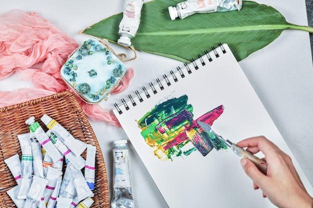 Mão de mulher desenhando imagem de pintura com tintas a óleo.