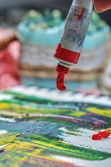 Mão de mulher desenhando quadro de pintura com tubos de pintura.