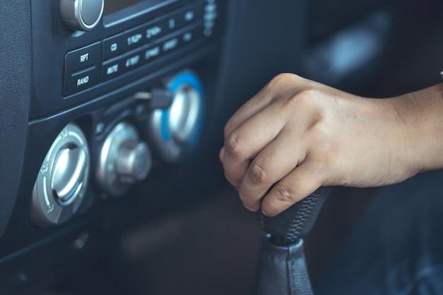 Mão de mulher, deslocando a alavanca de câmbio enquanto estiver dirigindo um carro em tom de cor vintage