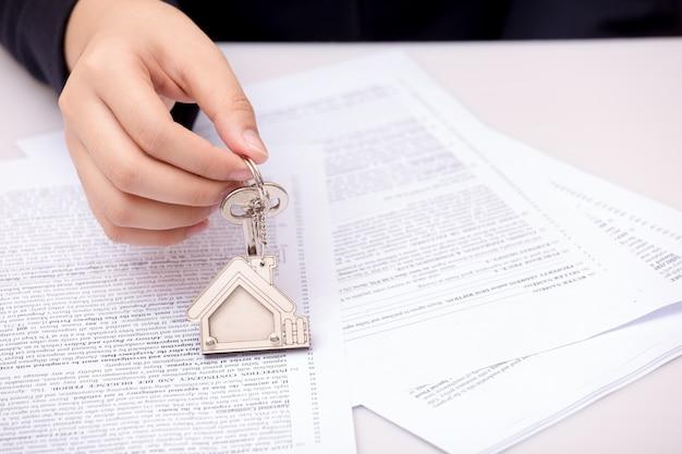 Mão de mulher e chave de casa. contrato assinado e chaves da propriedade com documentos