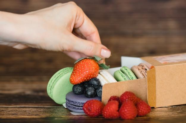 Mão de mulher e macarons com frutas frescas na superfície de madeira
