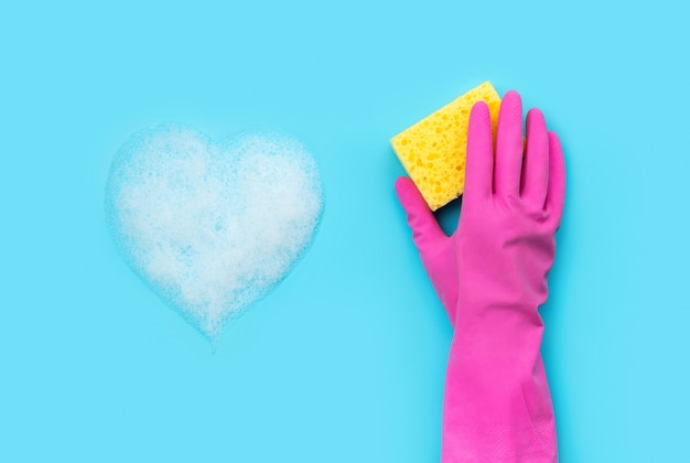 Mão de mulher em luva de borracha rosa lavada por esponja de fundo azul