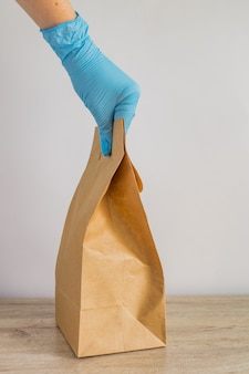 Mão de mulher em luvas de látex azuis segurando o saco de papel descartável de artesanato para entrega. entrega segura durante o isolamento do coronavírus