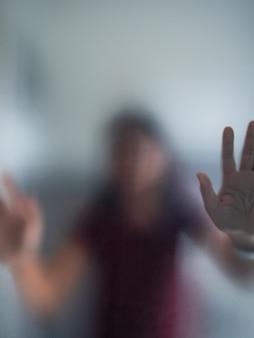 Mão de mulher embaçada por trás do vidro fosco metáfora pânico e emocional escuro negativo