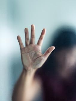 Mão de mulher embaçada por trás do vidro fosco metáfora pânico e negativo escuro emocional