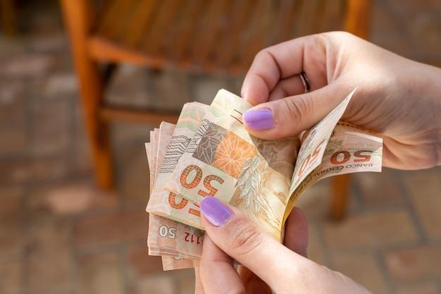 Mão de mulher entregando cédulas de dinheiro brasileiro