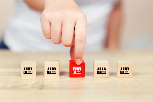 Mão de mulher escolher blog de madeira com marketing de franquia.