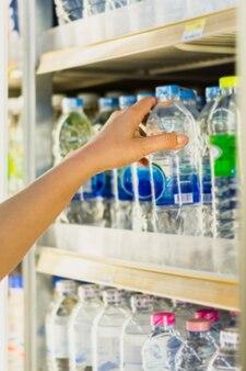 Mão de mulher escolher produto de prateleiras de geladeira de loja de conveniência