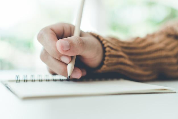 Mão de mulher escreva no caderno de memorando branco para tomar uma nota para não esquecer, fazer a lista ou planejar o trabalho no futuro na mesa de trabalho.