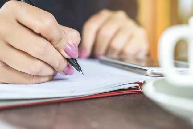 Mão de mulher escrevendo algumas idéias no caderno