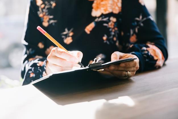 Mão de mulher escrevendo na agenda de consultoria