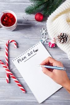 Mão de mulher escrevendo no bloco de notas saudações de natal com decoração em madeira